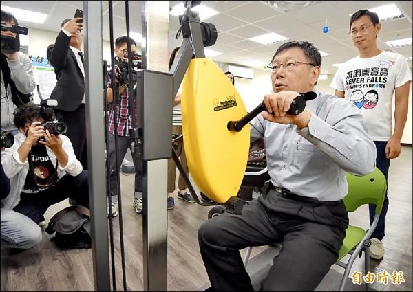 ▲台北市長柯文哲昨參觀信義身障社區長照機構,體驗升降式健身車。(記者簡榮豐攝)