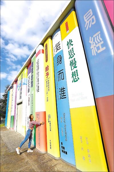 在2層樓高的巨無霸書冊外,可挑本喜愛的書籍合影。(記者李惠洲/攝影)