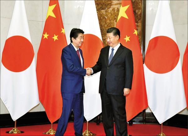 日本首相安倍晉三於25至27日訪問中國3天,26日在北京釣魚台國賓館與中國國家主席習近平(右)舉行「安習會」,雙方會前先握手致意。(美聯社)