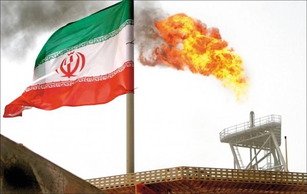 豎立在伊朗波斯灣索羅什油田的伊朗國旗,以及採油平台上的熊熊火焰。(路透檔案照)