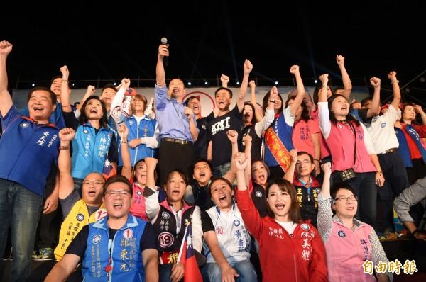 國民黨高雄市長候選人韓國瑜26日晚在「三山大會師」鳳山場,帶領候選人在台上高呼口號,現場旗海飄揚,現場民眾幾近瘋狂大喊韓國瑜「凍蒜」。(資料照)