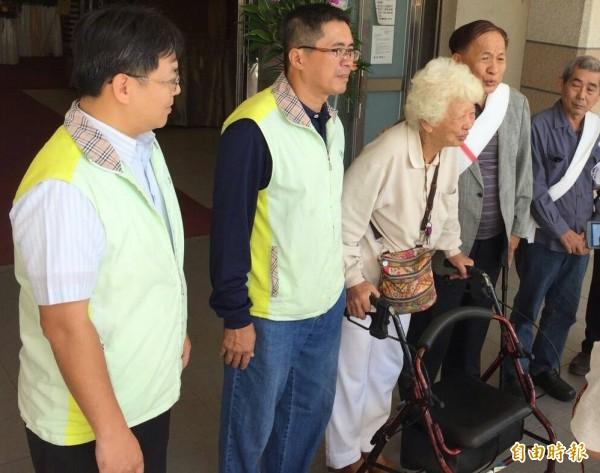 伴夫屍9個月的阿嬤陳妻(左三)拄著助行器,由殯葬管理處長謝汀嵩(左二)及家屬陪伴,向關心的親友、媒體鞠躬道謝。(記者黃良傑攝)