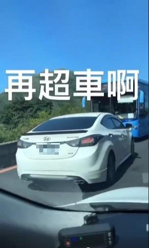 影片中一台白色轎車在山路疑似因為想要超車而開到對向車道上,不料前方一台公車駛來令白色轎車進退不得,只好慢慢倒車,場面十分尷尬。(圖擷取自臉書)