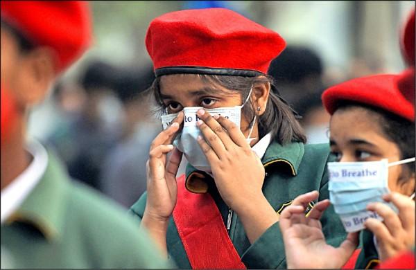 印度新德里學童配戴口罩,參加反空污遊行活動。(法新社檔案照)