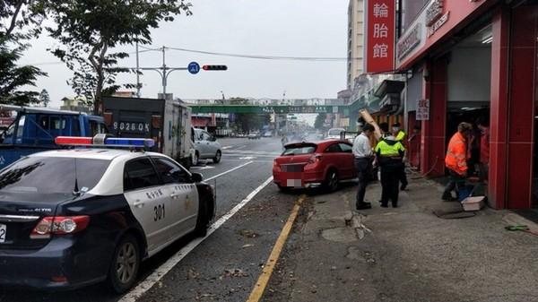 警方到場處理,研判紅色轎車因超車不慎自撞路旁輪胎行。(記者彭健禮翻攝)