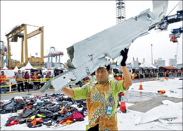 雅加達丹戎不碌港的工作人員,二日將尋獲的客機殘骸搬上卡車。(路透)