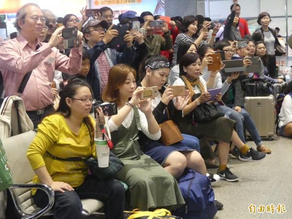 張正傑帶著音樂家在金門機場「快閃」,許多旅客聞聲紛紛拿起手機「全都錄」。(記者吳正庭攝)