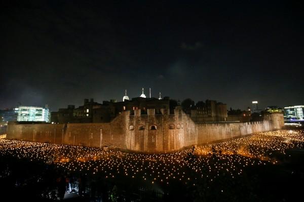 4日晚間,倫敦塔點燃1萬隻火焰紀念一次世界大戰結束百年。(路透)