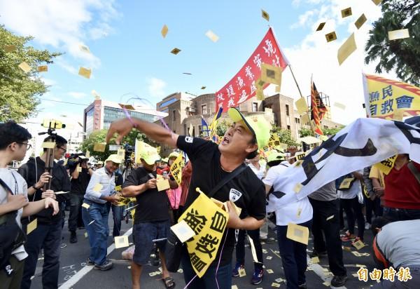 上千名來自蘇澳、琉球、東港等地漁民6日北上,自農委會遊行至立法院,抗議政府無力守護台灣漁權,導致漁民生計遭受重創,在農委會前撒冥紙表達不滿情緒。(記者羅沛德攝)
