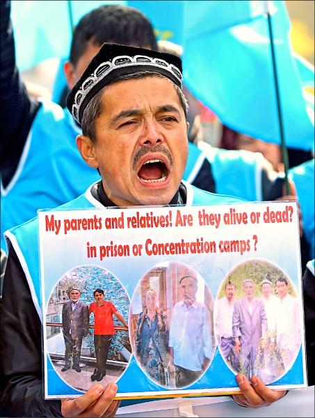 聯合國人權理事會六日在瑞士日內瓦對中國人權進行普遍定期審議,一名維吾爾族男子在場外舉起標語,抗議中國高壓統治新疆。(路透)
