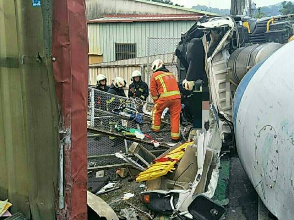 圖為混凝土車過彎逆衝對向民宅後翻覆,司機一度受困車內,消防人員合力救援。(記者李容萍翻攝)