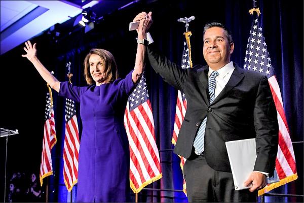 美國國會眾議院民主黨領袖裴洛西(左),六日晚間在勝選派對上,拉起民主黨國會競選委員會主席盧漢的手,慶祝民主黨重返眾院多數黨寶座。(法新社)