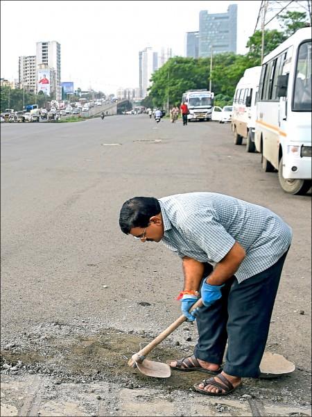 達德勞爾.比爾霍爾(Dadarao Bilhore)的兒子因路面坑洞意外喪生,他決心填平孟買凹凸不平的道路,避免憾事重演。 (法新社檔案照)