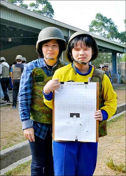 全盲生陳椘芸(右)打中三發,高興展示打靶成績。(記者楊金城翻攝)