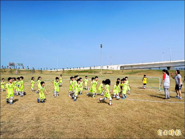 新竹市府在南寮閒置土地上闢設運動公園,有標準的足球場和練習場,昨天竣工。圖為小朋友開心踢足球。(記者洪美秀攝)