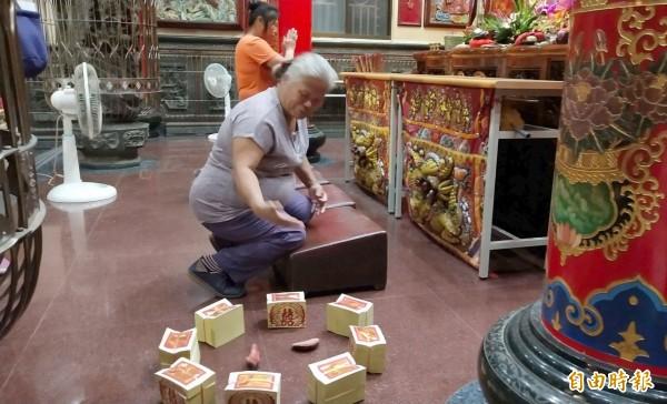擲出立筊的毛姓婦人今晚又來拜媽祖,模擬昨晚的擲筊手勢,還是不知道如何擲出立筊。(記者楊金城攝)