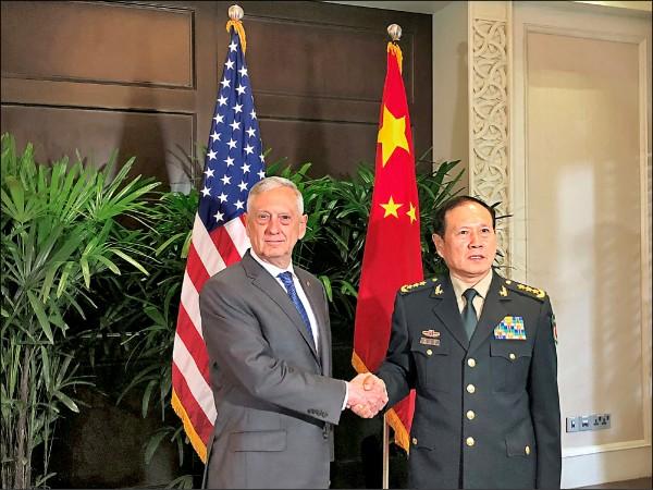 美國防部長馬提斯(左)上月十八日在新加坡與中國國防部長魏鳳和(右)晤談前握手致意。這是兩人不到五個月內的第二次會晤,九日則是第三次,密集程度甚為罕見。(路透檔案照)