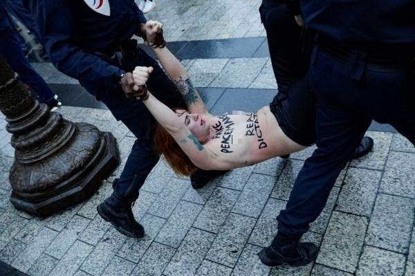 抗議女子遭警方抬離現場。(法新社)