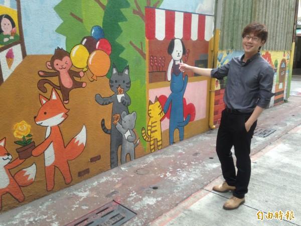 陳冠榮為社區彩繪感到驕傲。(記者黃旭磊攝)
