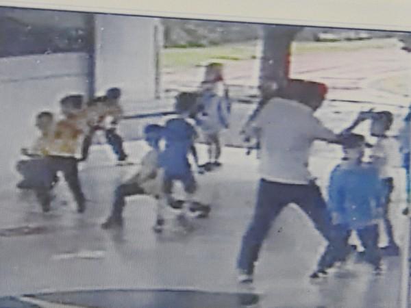 監視器畫面中薛姓體育老師對學童巴頭。(記者佟振國翻攝)