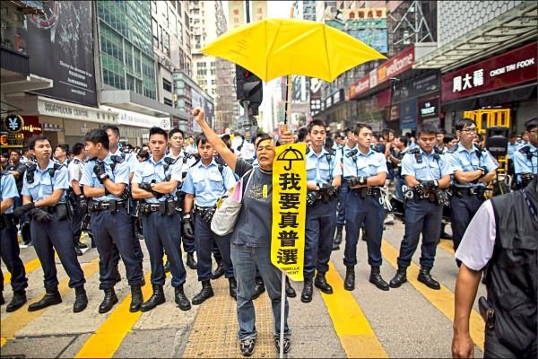 二○一四年十一月下旬,一名參與佔中行動的抗議者站在一排警察前,高舉黃色雨傘和標語,高呼要真普選。(歐新社檔案照)