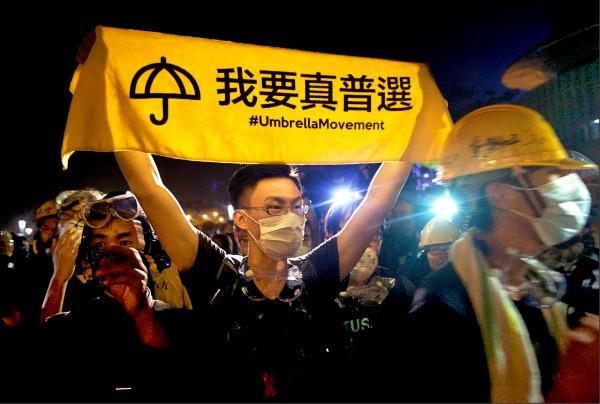 中國政府持續侵害香港自治權,打壓港人言論自由,「直接介入」美國引渡滯港罪犯等香港內部事務,美國會傳建議評估是否應將香港、中國視為同一關稅區。圖為2014年香港雨傘運動期間,一名港青「我要真普選」布條。(歐新社檔案照)