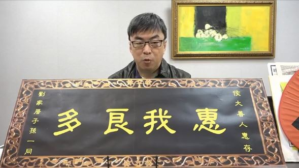 段宜康拿著寫著「惠我良多」的特製匾額,諷刺表示要代替劉家人感謝侯友宜「熱心善良」幫他們找回失散多年的親人。(圖擷取自段宜康臉書)