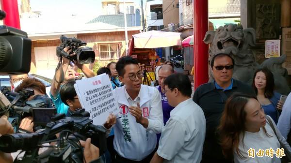 基進黨候選人李宗霖高舉承諾書紙板堵人,但被高思博的支持者阻隔。(記者蔡文居攝)
