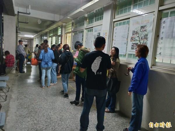 台北市永吉國中投票所還有民眾等著排隊投票,排最後一位的等到5點半還在等。(記者蔡亞樺攝)