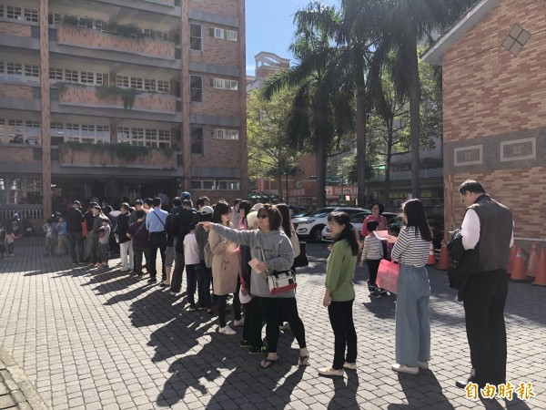 光明國小投票排隊人潮是從教室一路快排到校門口。(記者魏瑾筠攝)