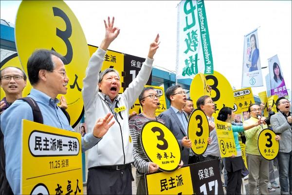 香港泛民主派候選人李卓人(左2)與支持者,25日在街頭高呼口號拉票。(美聯社)