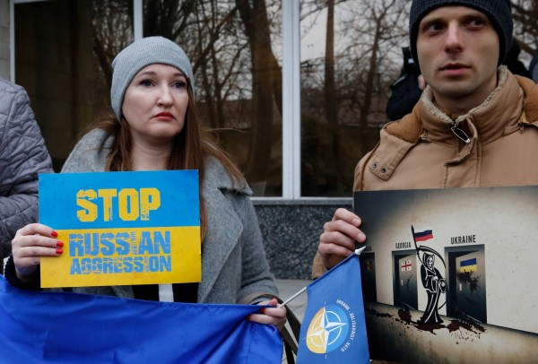 俄羅斯不但不理會國際間要求釋放烏克蘭海軍船隻的要求,反而指控烏克蘭挑起爭端。圖為烏克蘭民眾舉標語抗議俄羅斯的侵略行動。(路透)