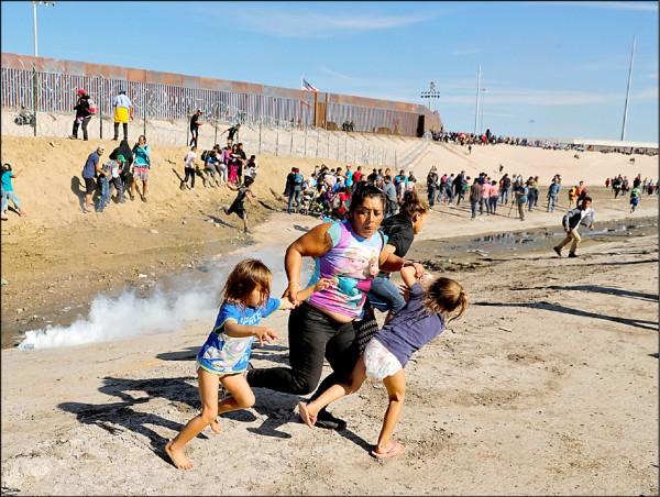 美國邊境官員二十五日在蒂華納施放催淚瓦斯,驅趕企圖衝向美墨邊界圍牆的群眾,一名母親在混亂中急忙牽著兩個孩子逃跑。(路透)