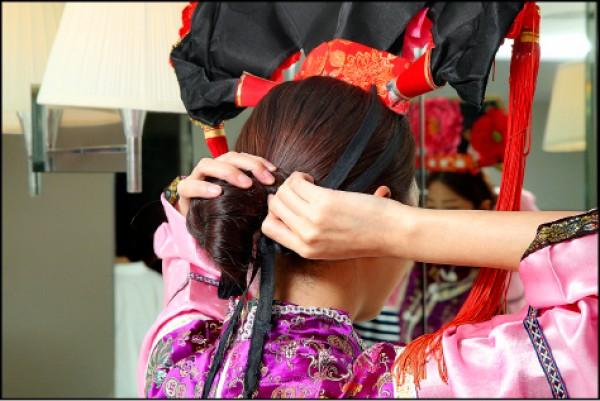 先梳包頭或是綁辮子,更能有利於牢牢地固定頭飾在頭髮上。(記者沈昱嘉/攝影)