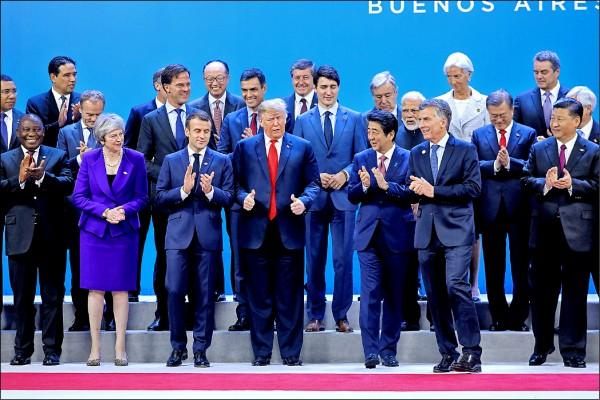 二十國集團(G20)峰會首日,各成員國領袖依慣例拍攝大合照。站在舞台中央的美國總統川普雙手豎起大拇指。(法新社)