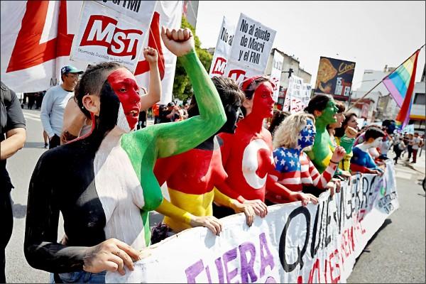 數以千計的民眾十一月三十日在阿根廷布宜諾斯艾利斯發起反二十國集團(G20)示威。圖為一群赤裸上身、彩繪峰會成員國國旗圖案的婦女,在當局劃設的示威區域,向各國領袖表達抗議。他們指責G20國家的政策根本「分裂世界」,直呼「打倒資本主義、打倒G20」。(歐新社)