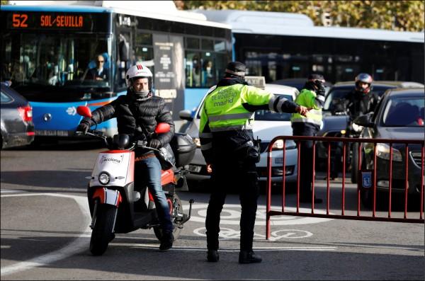西班牙首都馬德里為了改善空污,劃設「馬德里中心」管制區,試行市中心車輛管制計畫。圖為一輛機車騎過標有「馬德里中心」的路面。(路透)