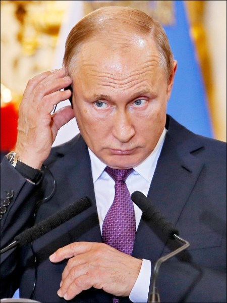 參加阿根廷年度二十國集團(G20)峰會的俄羅斯總統普廷,一日與阿國總統馬克里舉行會談。圖為普廷在會後的聯合記者會上調整耳機。(美聯社)