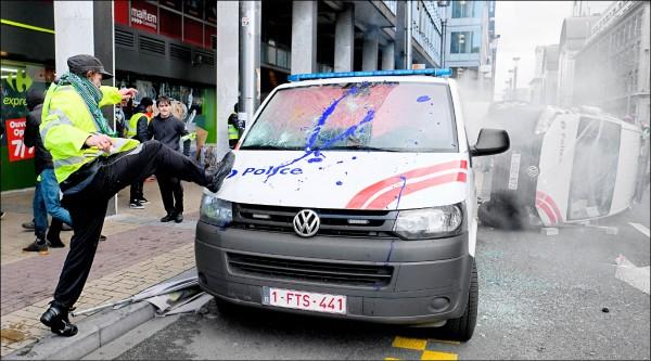 比利時黃背心抗議人士推倒警車,並縱火焚燒。(歐新社)