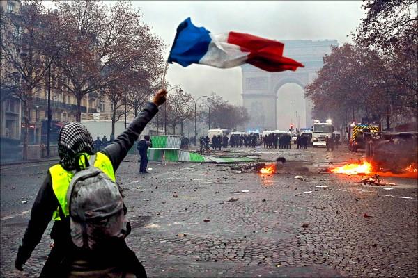 抗議政府調漲燃料稅的法國「黃背心」運動,一日再現暴力。鎮暴警察在巴黎市中心的凱旋門嚴陣以待,穿著螢光黃背心民眾則在不遠處揮舞國旗示威。(歐新社)