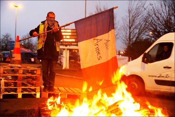 不滿燃料稅等生活成本節節高升,穿上法國司機必備「黃背心」的示威者,四日在通往比利時的法國公路旁焚燒法國國旗,與政府「奮戰」。(路透)
