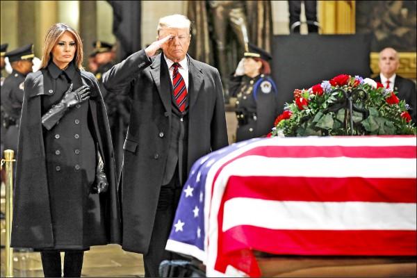 總統川普偕同第一夫人梅蘭妮亞,前往老布希靈柩前敬禮致意。(彭博)