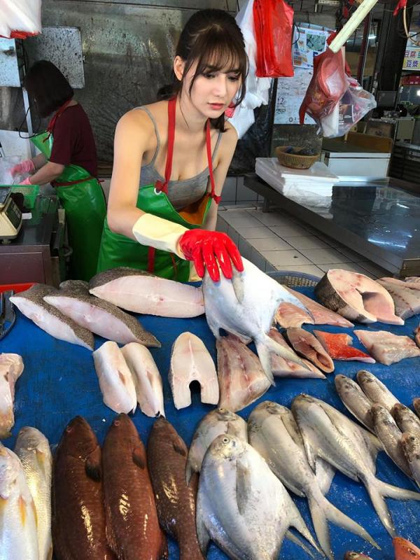 只見照片中賣魚正妹容貌艷麗,穿著一件灰色的細肩帶低胸背心,相當性感。(圖擷取自臉書「爆廢公社二館」)