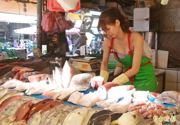 阿澎手腳俐落的幫顧客處理魚貨。(記者陳冠備攝)