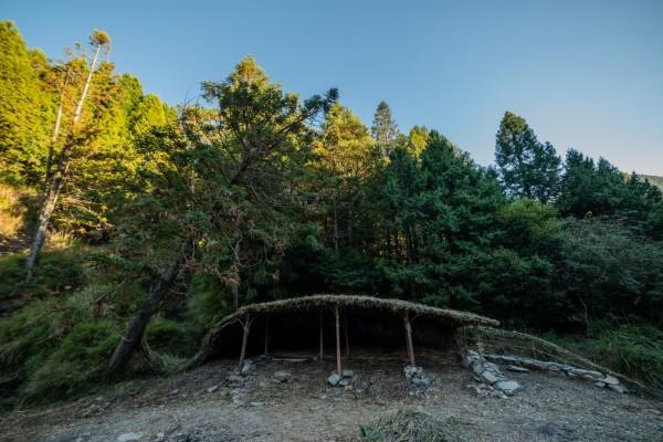 新竹縣參加「山學校」大地藝術工作營的泰雅兒童,把山林裡的簡陋獵寮改造成融合河流、獵刀意象的獵人庇護所。(圖由Wagi Qmisan提供)