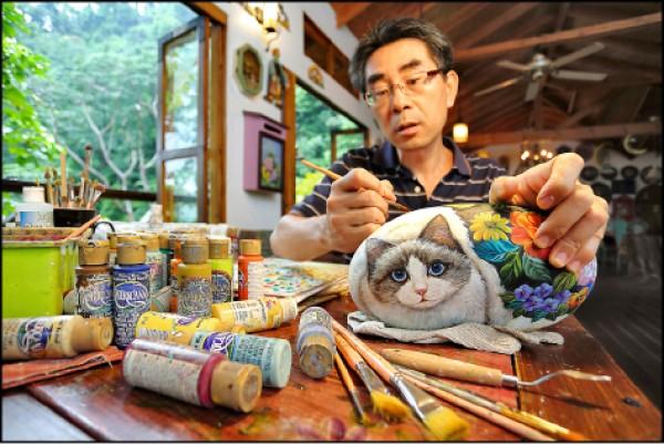 劉順光運用畫筆揮灑繽紛色彩,將常見無奇的石頭變成靈動活潑的貓咪(記者李惠洲/攝影)