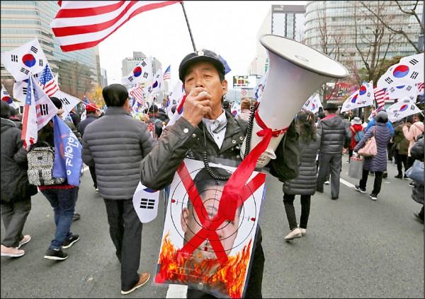 反對北韓政權及其領導人金正恩的一名南韓抗議人士,在首爾參加示威遊行,身上揹著象徵鎖定金正恩攻擊的自製海報。(美聯社檔案照)