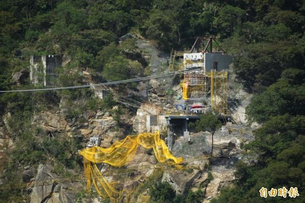 山月吊橋因施工難度高,北端地形崎嶇複雜,工程人員均需自溪谷垂直爬上山後進入工地,材料機具則以流籠推進。(記者王峻祺攝)