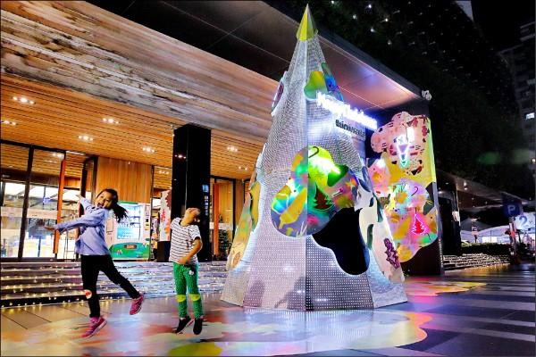 6.5米高的「璀璨聲光聖誕樹」繽紛地讓小朋友開心合照。(記者李惠洲/攝影)