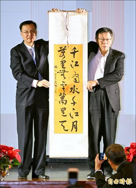 雙城論壇晚宴昨在圓山飯店舉行,中國上海市副市長周波(左)回贈台北市長柯文哲(右)「千江有水千江月,萬里無雲萬里天」書法條幅。(記者黃耀徵攝)
